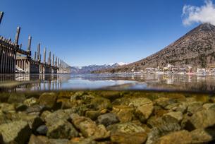 中禅寺湖の崩れかけた桟橋と水中の半水面風景の写真素材 [FYI04737353]