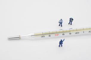 39℃の体温計を見て指摘する警察官のミニチュア の写真素材 [FYI04737601]
