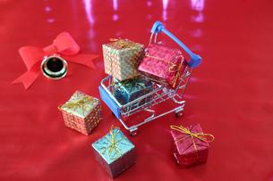 赤い布に置いたクリスマスプレゼントとミニチュアのショッピングカートの写真素材 [FYI04737608]
