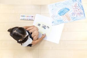 フローリングの床で大きな画用紙に絵を描いて遊ぶ1人の幼い女の子の俯瞰の写真素材 [FYI04738637]