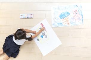 フローリングの床で大きな画用紙に絵を描いて遊ぶ1人の幼い女の子の俯瞰の写真素材 [FYI04738640]