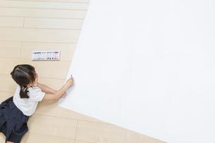 フローリングの床で大きな白紙に絵を描き始める1人の幼い女の子の俯瞰。コピースペース用の白紙の写真素材 [FYI04738642]