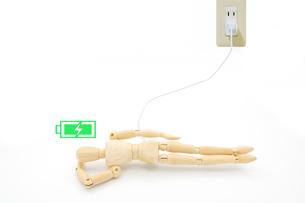 横になって充電するデッサン人形の写真素材 [FYI04738704]