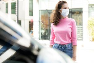自動車の前で立つフェースマスク姿の若い女性の写真素材 [FYI04738792]