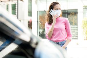 自動車の前で立って携帯電話を使っているフェースマスク姿の若い女性の写真素材 [FYI04738793]