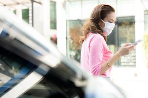 自動車の前で立って携帯電話を使っているフェースマスク姿の若い女性の写真素材 [FYI04738795]