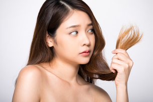 ダメージヘアで困っている若い女性の写真素材 [FYI04739222]