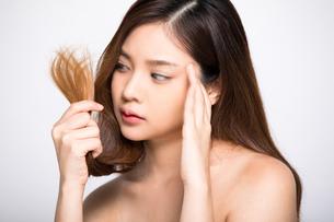 ダメージヘアで困っている若い女性の写真素材 [FYI04739224]