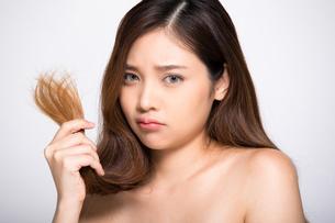 ダメージヘアで困っている若い女性の写真素材 [FYI04739225]