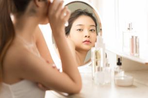 スキンケアしている若い女性の姿のミラー反射の写真素材 [FYI04739230]
