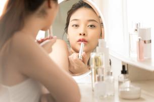スキンケアしている若い女性の姿のミラー反射の写真素材 [FYI04739231]