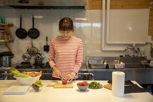共同キッチンで調理する女性の写真素材 [FYI04739474]