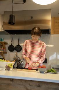 共同キッチンで調理する女性の写真素材 [FYI04739476]