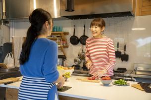 共同キッチンで調理する女性の写真素材 [FYI04739483]
