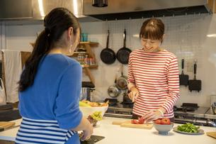 共同キッチンで調理する女性の写真素材 [FYI04739484]