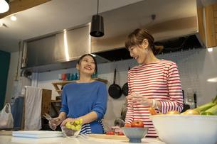共同キッチンで調理する女性の写真素材 [FYI04739530]