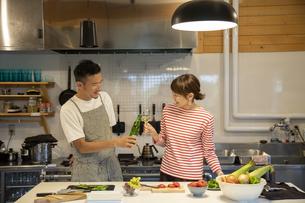共同キッチンで調理する男女の写真素材 [FYI04739535]