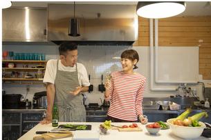 共同キッチンで調理する男女の写真素材 [FYI04739539]