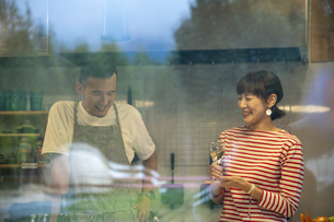 共同キッチンで談笑する男女の写真素材 [FYI04739540]