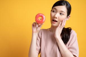 おいしそうなドーナツをすすめる若い女性の写真素材 [FYI04739590]