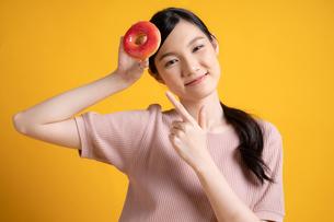 おいしそうなドーナツをすすめる若い女性の写真素材 [FYI04739591]