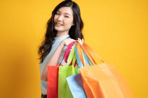 たくさん買い物して満足そうな若い女性の写真素材 [FYI04739594]
