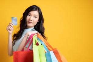 クレジットカードでたくさん買い物をした若い女性の写真素材 [FYI04739596]