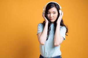 ワイヤレスヘッドフォンで音楽を楽しんでいる若い女子大生の写真素材 [FYI04739597]