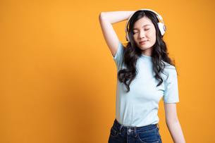 ワイヤレスヘッドフォンで音楽を楽しんでいる若い女子大生の写真素材 [FYI04739598]