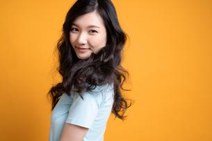 黄色のバックアップの前で立っている若い女性モデルの写真素材 [FYI04739599]