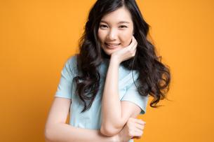 黄色のバックアップの前で立っている若い女性モデルの写真素材 [FYI04739600]