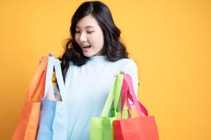 カラフルな買い物袋を持っている幸せそうな若い女性の写真素材 [FYI04739601]