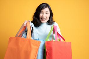 カラフルな買い物袋を持っている若い女性の写真素材 [FYI04739602]