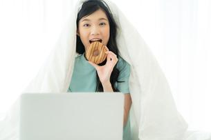 ベッドでパソコンを見ながらドーナツを食べる若い女性の写真素材 [FYI04739603]