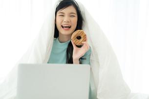 ベッドでパソコンを見ながらドーナツを食べる若い女性の写真素材 [FYI04739604]