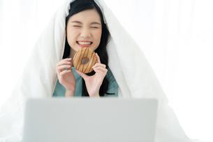 ベッドでパソコンを見ながらドーナツを食べる若い女性の写真素材 [FYI04739605]