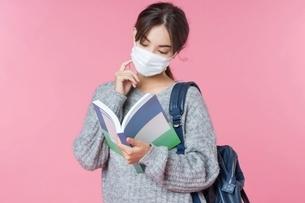 マスク姿で教科書を読んでいる女子大生の写真素材 [FYI04739612]