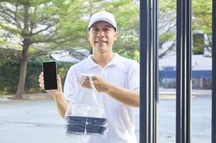 男性配達員が携帯電話の画面を見せながら荷物の受取を持つの写真素材 [FYI04739641]