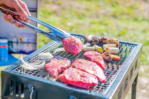 屋外のオープングリルで牛肉を網焼きしている様子の写真素材 [FYI04739984]