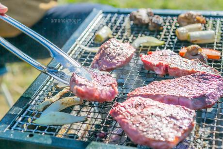 屋外のオープングリルで牛肉を網焼きしている様子の写真素材 [FYI04740000]