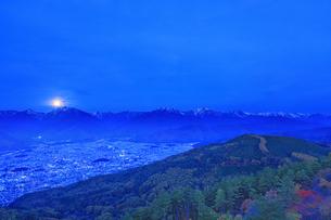鷹狩山から望む北アルプスと大町市街と夜明けの月の写真素材 [FYI04740665]