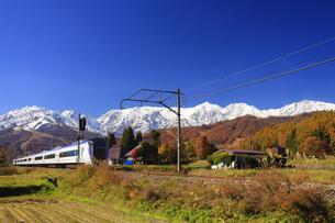 信濃森上駅付近を走る特急あずさと白馬連峰の写真素材 [FYI04740688]