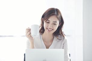 ノートパソコンで仕事をするスーツを着た若い日本人女性の写真素材 [FYI04741273]