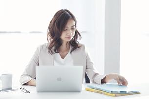 ノートパソコンで仕事をするスーツを着た若い日本人女性の写真素材 [FYI04741285]