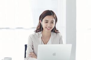 イヤホンをしてノートパソコンで仕事をするスーツを着た若い日本人女性の写真素材 [FYI04741292]