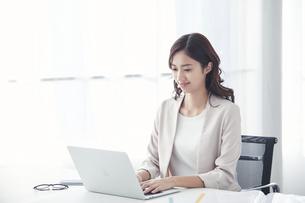 ノートパソコンで仕事をするスーツを着た若い日本人女性の写真素材 [FYI04741308]
