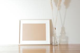 シンプルなインテリアの飾りと写真フレームのオブジェクトのレイアウト。卓上植物、パンパスグラスの写真素材 [FYI04741356]