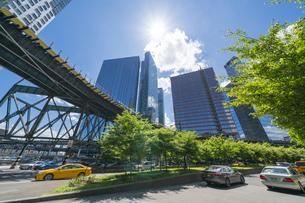 ニューヨーク市 ロングアイランドシティー クイーンズボロープラザの 新緑の並木道沿い高層ビル群の間を走るニューヨーク市地下鉄。の写真素材 [FYI04741405]