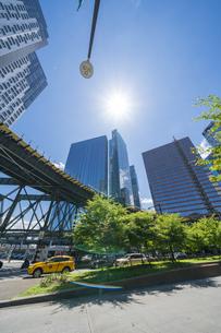 ニューヨーク市 ロングアイランドシティー クイーンズボロープラザの 新緑の並木道沿い高層ビル群の間を走るニューヨーク市地下鉄。の写真素材 [FYI04741411]