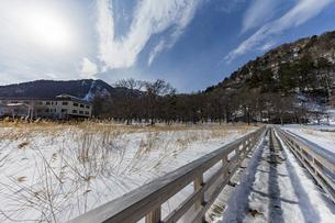 雪解けが進む湯ノ平湿原に架かる木道と太陽の写真素材 [FYI04743252]